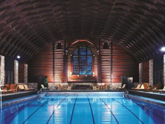 Indoor pool at Fairmont Le Chateau Montebello under a vaulted wooden ceiling