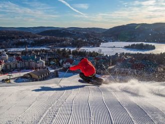Skiier going down slope towards Fairmont Tremblant