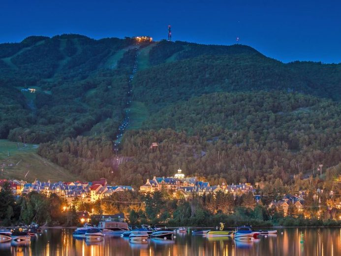 Aerial view of Fairmont Tremblant and ski hill in the background at twilight