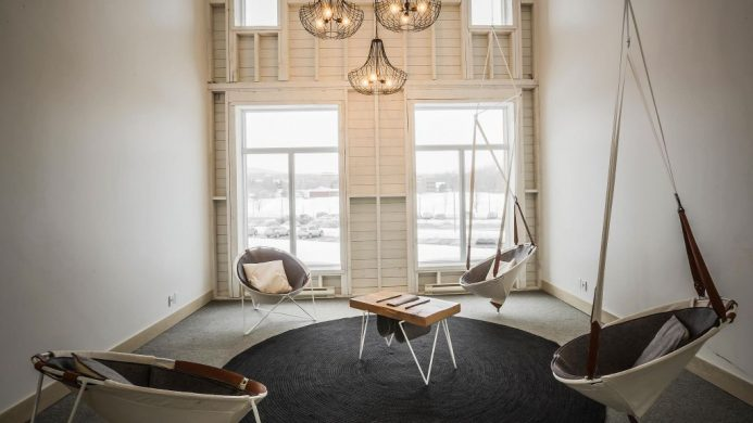 White lounge room with swing chairs at Le Germain Charlevoix Hotel