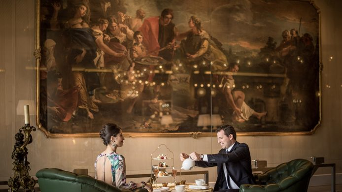 Couple having tea in front of oil painting at Rome Cavalieri hotel