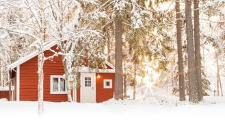 Loggers Lodge's red cabin in the forest covered in snow
