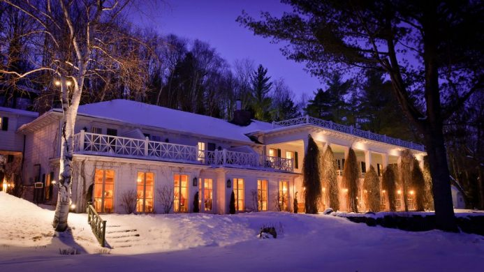 Exterior of Manoir Hovey at night in the snow