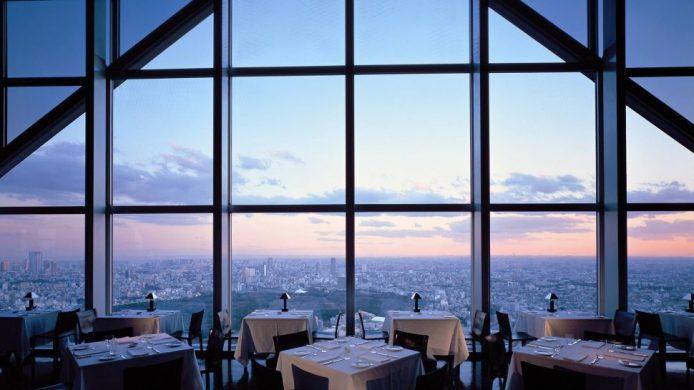 Park Hyatt Tokyo's restaurant dining room with high windows framing city of Tokyo