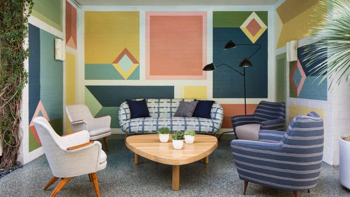 Avalon Hotel Beverly Hills outdoor seating with mid-century furniture against a colorful wall
