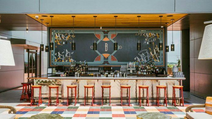Bobby Hotel's bar counter with an Art Deco-style backsplash and rainbow floor tiles