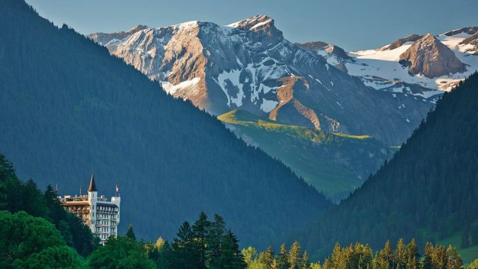 Gstaad Palace's towers peaking out from the forest under the Swiss mountains