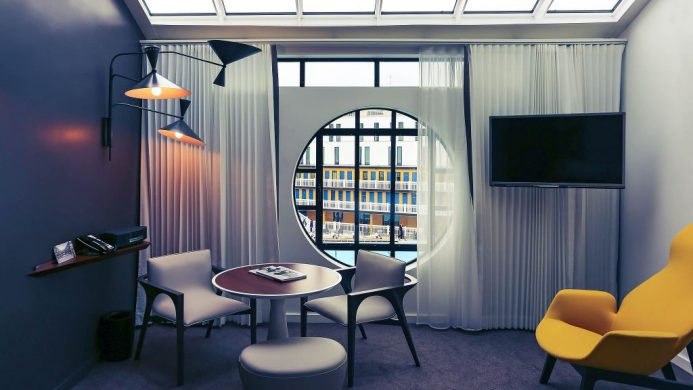 Hôtel Molitor Paris' room with a circular window looking out towards the courtyard pool
