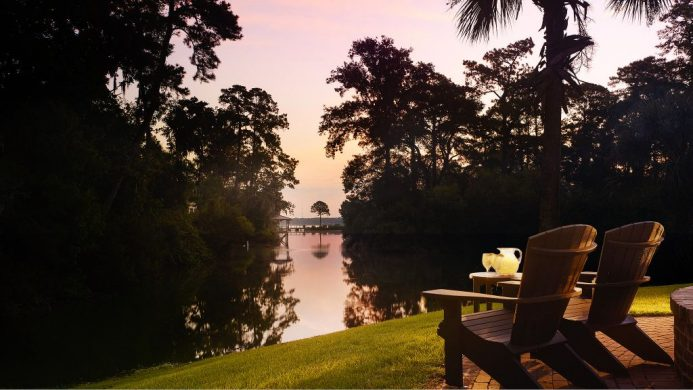 Adirondack chairs on a green lawn on the riverfront under a pink sky at Montage Palmetto Bluff