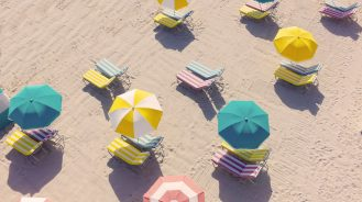 Aerial of candy color beach umbrellas on the beach at The Confidante hotel