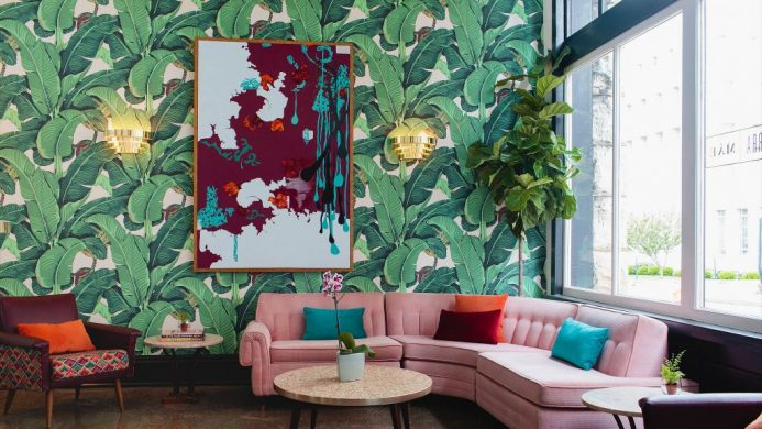 The Dwell Hotel's lounge a pink sofa and botanic wallpaper