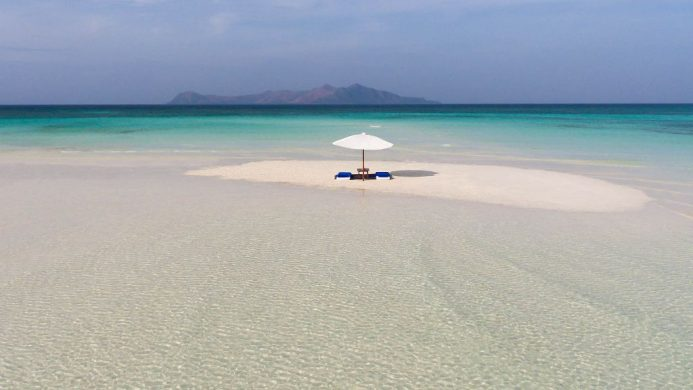 Deserted sandbar with only two chairs and an umbrella at Amanpulo resort