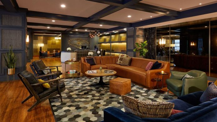 Hutton Hotel's lobby with wooden walls and a large leather sectional couch