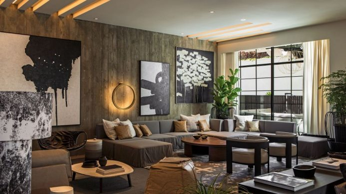 Kimpton La Peer Hotel's lobby living room with oversized sofas, potted plants and art hanging