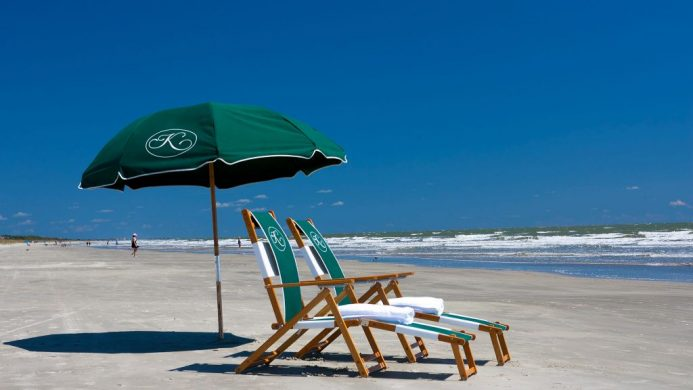 Quiet beach with two hotel-branded beach chairs under an umbrella on Kiawah Island