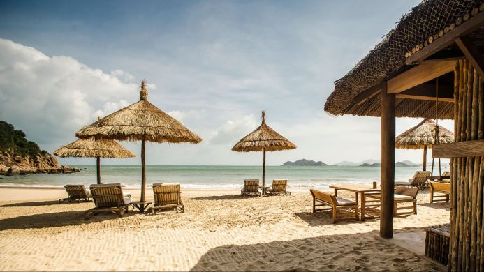 Zannier Hotels Bai San Ho's beach loungers under thatched umbrellas