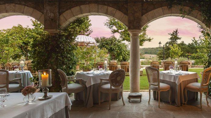 Borgo Santo Pietro Meo Modo Restaurant framed by arches overlooking a garden