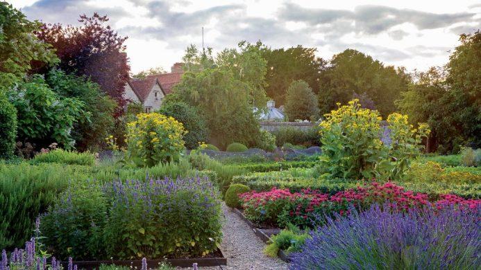 Le Manoir aux Quat'Saisons peeking out from behind a lush garden